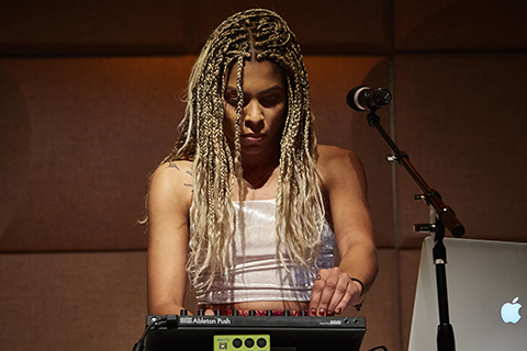 A woman with blonde braided hair adjusts a setting on a drum machine