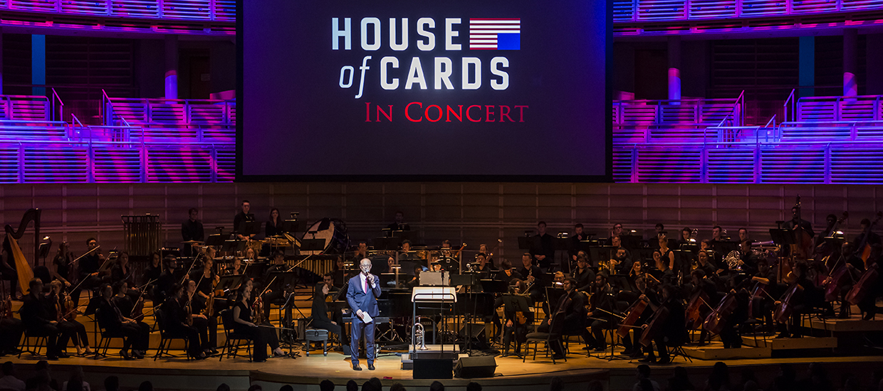 A man in a blue suit with a microphone is under the spotlight as a full orchestra sits down behind him with a House of Cards in Concert display in the back