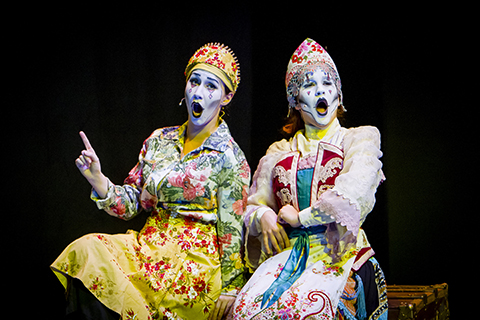 Two opera singers in bright colored clothes and white makeup sit on a bench as they sing in front of a black background