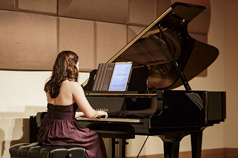 A woman in a maroon dress with long hair is playing a black Yamaha grand piano