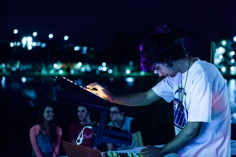 A man in a white t-shirt looks down as he is performing at night with a drum machine and keyboard