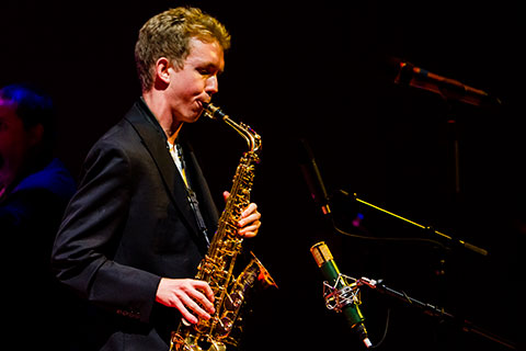 A man in a dark suit jacket is playing the saxophone in front of multiple multiple microphones