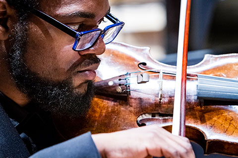 A close up image of a man with a beard and glasses playing the violin