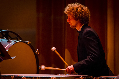 A man with curly hair and dark suit is playing the xylophone with 2 mallets he is holding in his hands.