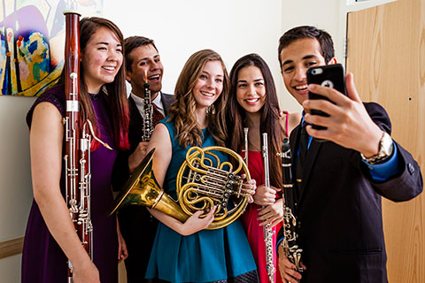 A group of students holding music instruments are taking a cellphone