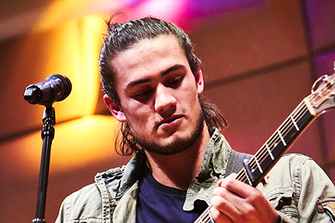 A man with long hair looks down as he plays the guitar behind a microphone