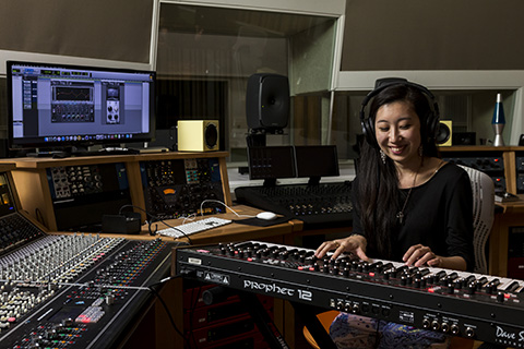 A woman wearing headphones plays the keyboard while sitting in a recording studio