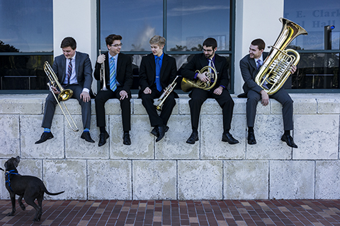 A group of musicians wearing suits are sitting on a wall as they are holding their musical instruments