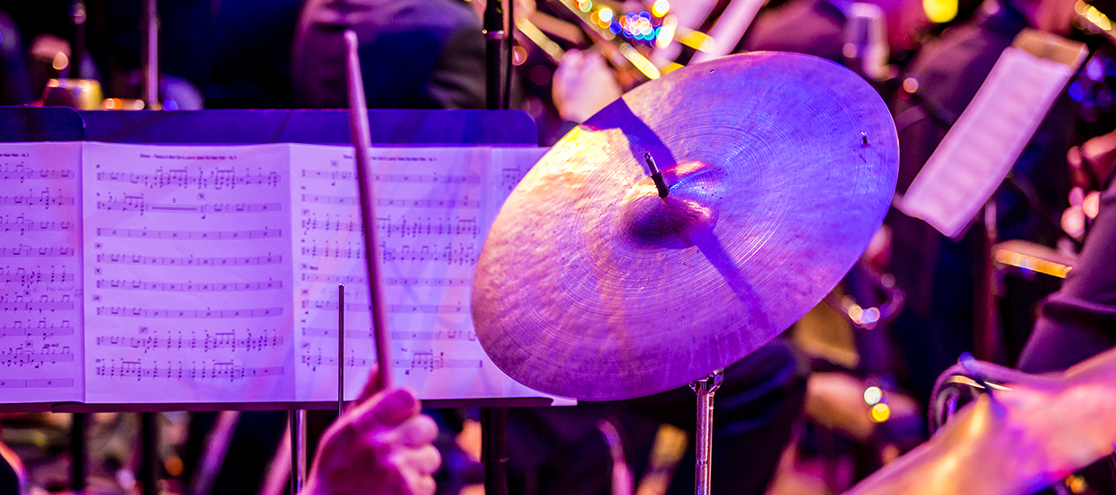 A drum stick heading towards a cymbal with sheet music being displayed in the background
