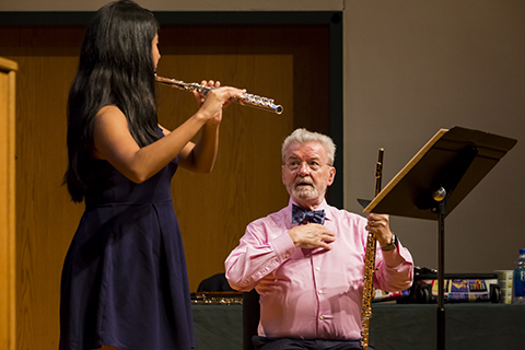 A student with long dark hair in a purple dress is playing the flute as a teacher looks on